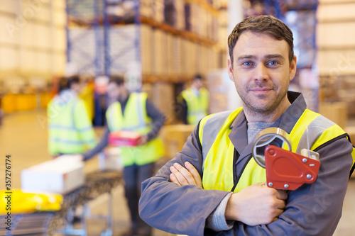 Cuadros en Lienzo Worker holding tape dispenser in warehouse
