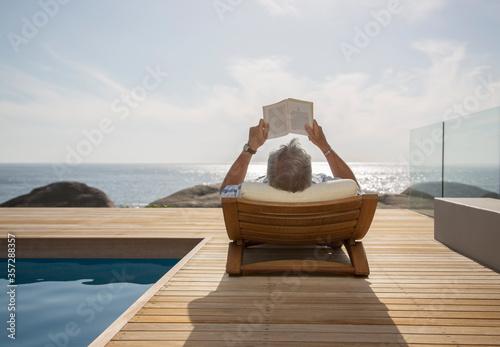 Valokuva Older man reading by pool
