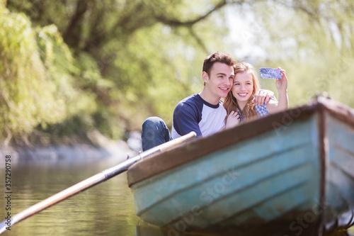 Fotografie, Obraz Couple taking self-portraits in rowboat