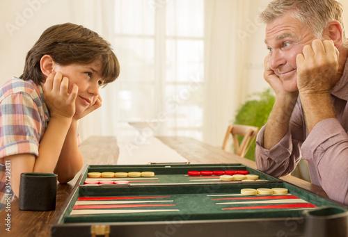 Obraz na plátne Grandfather and grandson playing backgammon