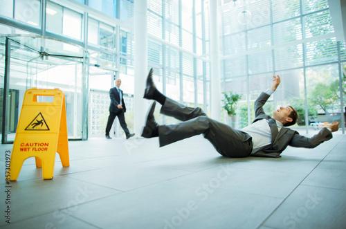 Businessman slipping on floor of office building Fototapet