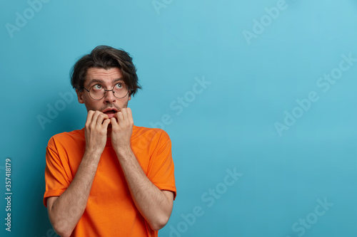Fotografia Scared nervous man bites finger nails and looks upwards with anxious expression,