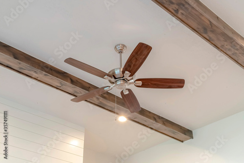 Photo Ceiling fan with lights between decorative wood beams inside living room of home