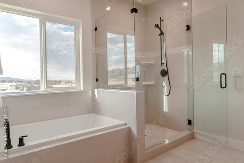 Built in bathtub with black faucet and shower stall with half glass enclosure Fototapeta
