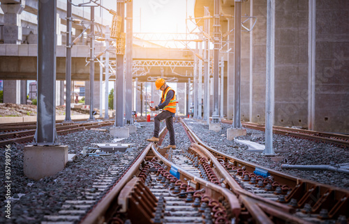 Photo Engineer under inspection and checking construction process railway switch and checking work on railroad station
