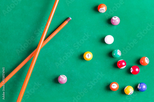 Obraz na plátně Billiard colorful balls with wooden cue on green table