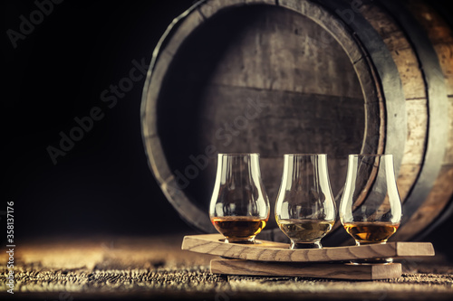 Fotografia, Obraz Glencairn whiskey tasting cups on a wooden serving, with a whisky barrel in the