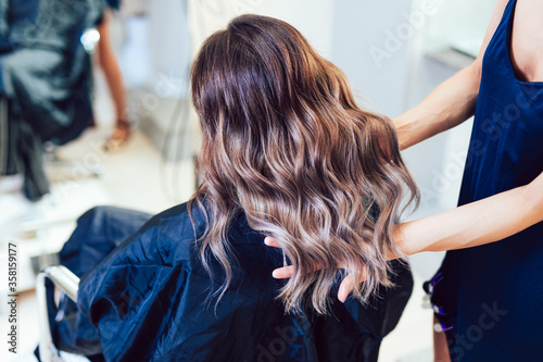 Canvas-taulu Young woman getting beautiful hairstyle in hair salon.