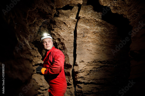 Photo Man walking and exploring dark cave with light headlamp underground