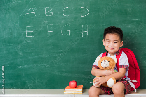 Back to School. Happy Asian funny cute little child boy from kindergarten in student uniform with school bag smiling and hugging teddy bear on green school blackboard, First time to school education