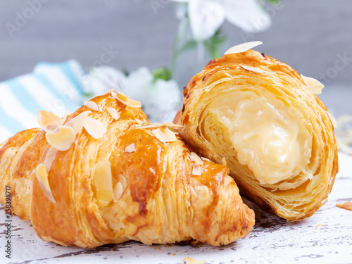 Fotografering Yummy freshly golden croissant with custard filling cut, close up