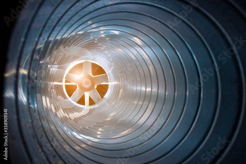 Fotomural closeup view from inside the galvanized steel air duct on the exhaust fan in the