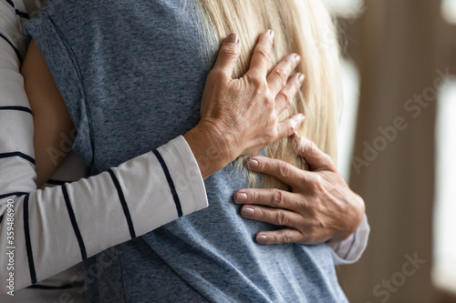 Fotografia Close up image elderly woman hugs younger relative girl