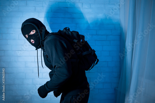 Canvastavla Sneaky scared robber ready to steal something at home