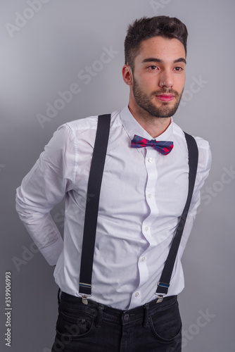 Leinwand Poster Young model in white shirt, suspenders, bow tie, piercings and fledgling beard
