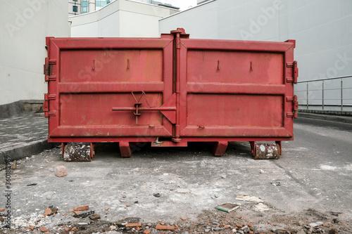 huge red metal garbage container between light walls of large buildings on backs Fototapet
