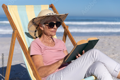 Canvastavla Senior Caucasian woman sitting on a deck chair and reading at the beach