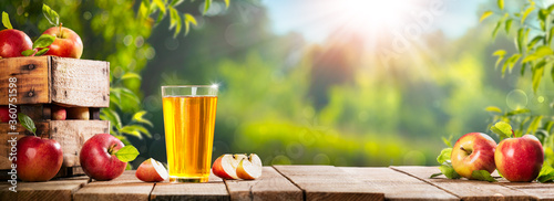 Fotografie, Tablou Apple Crate And Glass Of Juice On Wooden Table With Sunny Orchard Background - A