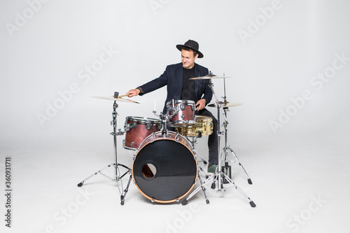 Vászonkép Young handsome man in hat and sunglasses playing drums isolated on white backgro