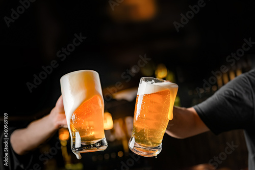 Fotografia two hands with beer mugs, toasting in celebration, with overflowing foam, dark b