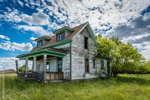 Canvas-taulu Old, abandoned prairie farmhouse with trees, grass and blue sky in Saskatchewan,