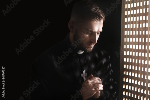 Fototapeta Young priest in confession booth