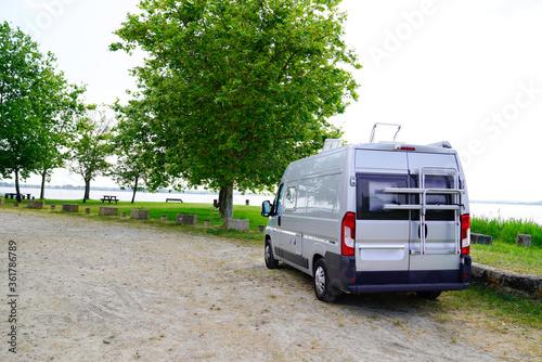 Fotografie, Tablou Motorhome RV campervan parked on a river side beach for night