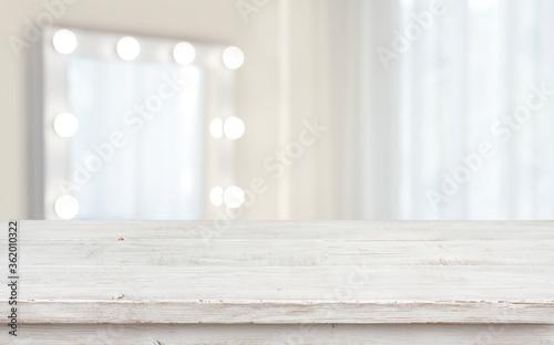 Defocused makeup mirror in dressing room with wooden table top Fototapeta