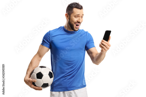 Obraz na płótnie Surprised soccer player holding a ball and looking at a mobile phone