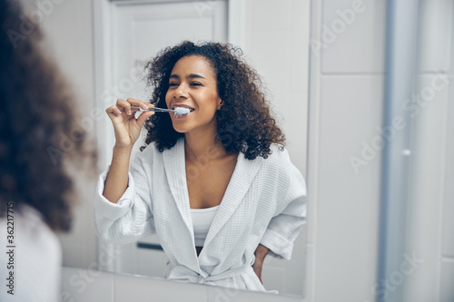 Fotografija Pleased curly-headed pretty lady brushing her teeth
