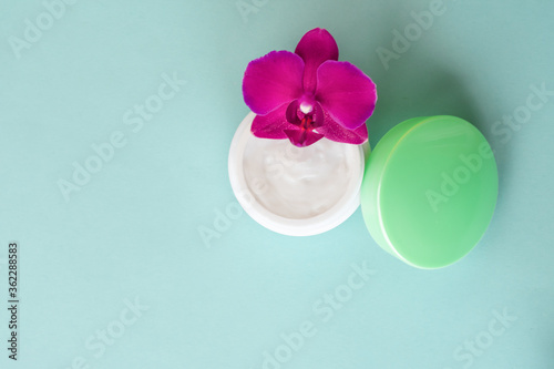 Cream in white jar with green cap on mint background with beautiful bright magenta orchid flowers. Soft cream with orchid extract for moisturizing skin. Eco cosmetic product, top view
