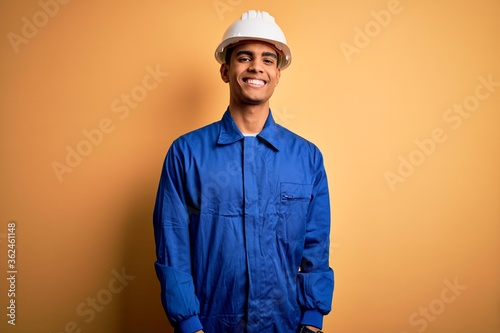 Obraz na plátně Young handsome african american worker man wearing blue uniform and security helmet with a happy and cool smile on face