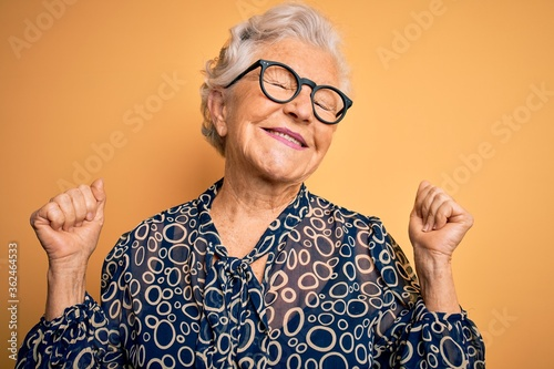 Fotografia, Obraz Senior beautiful grey-haired woman wearing casual shirt and glasses over yellow background very happy and excited doing winner gesture with arms raised, smiling and screaming for success