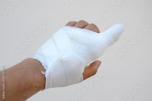 Leinwand Poster Cropped Patient Hand Wearing Bandage Against White Background