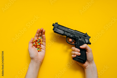 Valokuva Human hand holding a plastic toy gun and a bunch of plastic ball bullets on bright clean yellow background