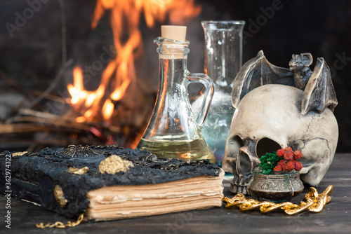 Fotografie, Obraz Magic potion and spell book on the table on burning fire in fireplace background