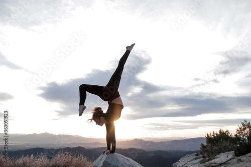 Fotografiet Woman Doing Handstand On Rock Against Sky