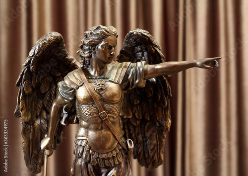 A bronze statuette of the Archangel Michael points a finger forward Fotobehang