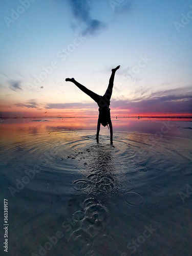 Fotografie, Tablou Handstand Of A Girl At Sunset In The Sea