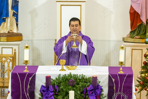 Fotografia, Obraz Priest Holding Wine While Standing At Table In Church