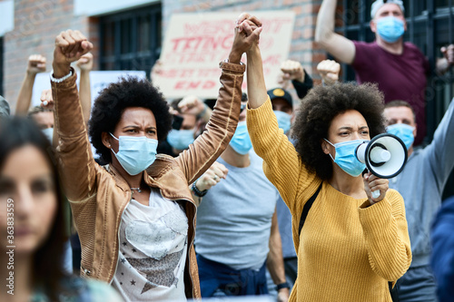 Fototapeta Black female activists holding hands while protesting with crowd of people during coronavirus pandemic