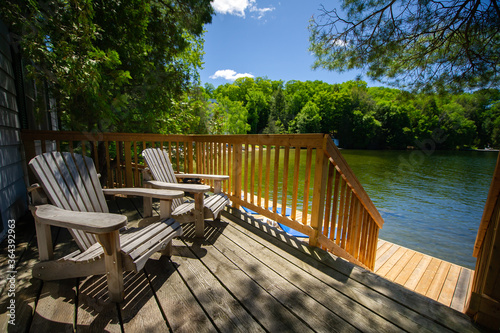 Adirondack chairs sitting on a cottage wooden deck facing a calm lake during a summer day in Muskoka, Ontario Canada Fototapet