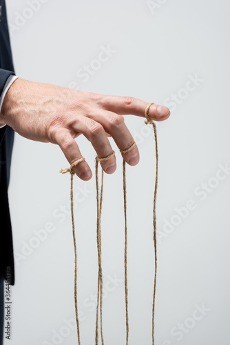 Canvas Print partial view of puppeteer with strings on fingers isolated on grey