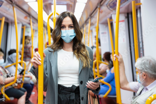Tela Enterprising young woman wearing a face mask travelling on public transport during rush hour