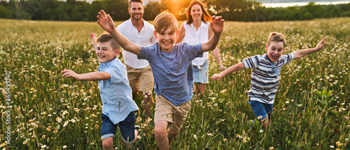Valokuva Happy family on daisy field at the sunset having great time together running tog
