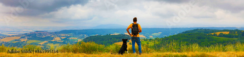 Canvas-taulu man backpacker with dog looking at landscape view, France- Auvergne