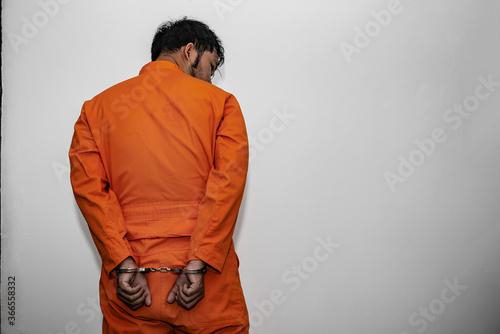 Fotografering Prisoner in orange robe concept,Portrait of asian handsome man in Prison uniform