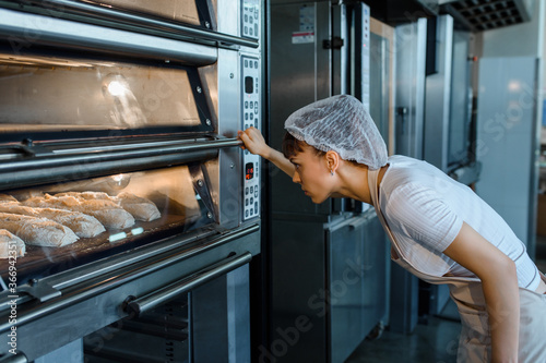 Fotografia Young caucasian woman baker is looking at the bread baker process in an electric oven at a baking manufacturing factory