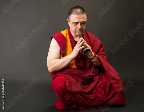 Fotografia Tibetan Buddhist monk teacher in a burgundy yellow outfit suit