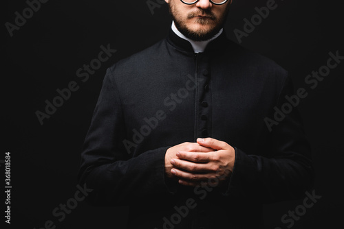 cropped view of priest with clenched hands isolated on black Fototapeta